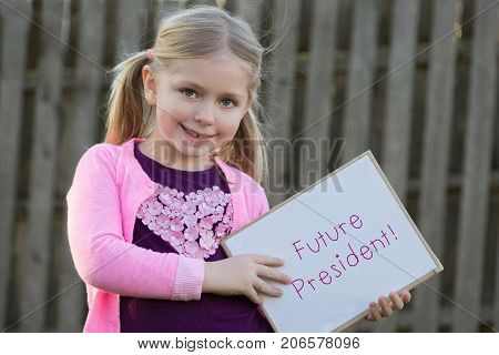 adorable school age girl wearing pink and holding sign that says future president for women's rights