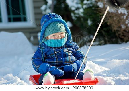 adorable toddler boy being pulled on sled outside in wintertime