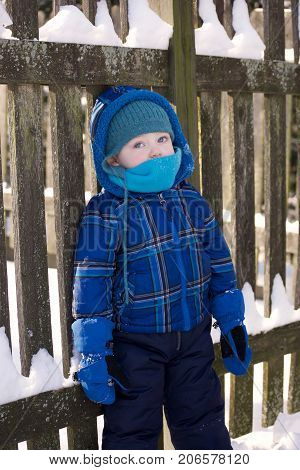 adorable toddler boy bundled up in hat scarf and winter coat leaning on fence with snow during wintertime