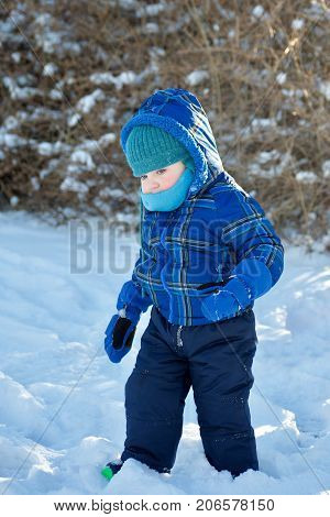 toddler boy bundled up in winter coat hat and scarf walking in snow outside