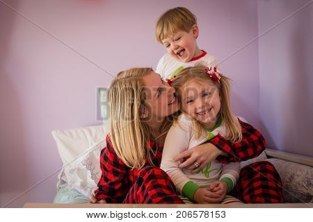 mother with son and daughter cuddling on bed together in Christmas Pajamas