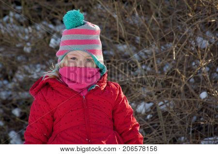 adorable school age girl standing in hat and scarf and winter coat with snow during wintertime
