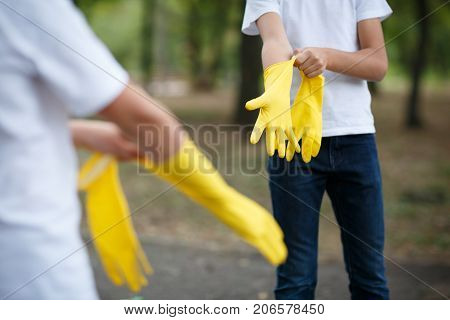 Team work of outdoors cleaning. Environmental protection. Closeup cropped portrait. Getting started cleaning. Yellow rubber cleaning gloves closeup. Workhouse concept. Helping team.