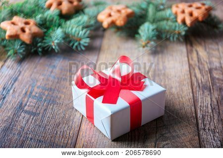 A little, white present box with a festive red bowtie next to Christmmas pine branch and sweets on a wooden table background.