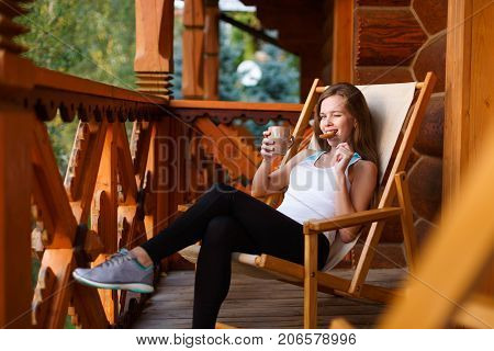 Young attractive woman sitting outdoors on deck chair with coffee cup and oat cookie at mountain resort. Female on chaise-longue with tea mug and snack. Diet concept. Green forest on background.