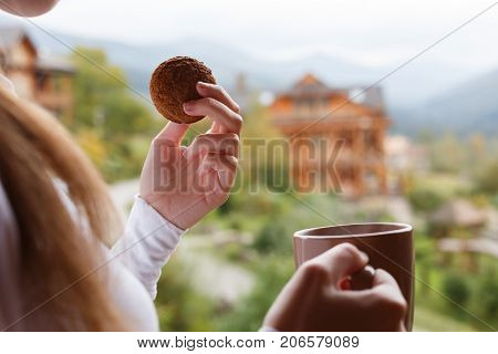 Woman holds cup of coffee and oat cookie in her hands at mountain resort. Female with tea mug and snack with forest and wooden hotel on background. Dietary concept.