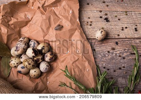 Top view of fresh speckled quail eggs, aromatic green twigs of rosemary, dried up bay leaves on a piece of grocery paper on a light wooden background.