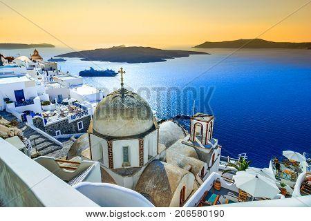 Fira, Santorini - Greek Islands landmark with white village, cobbled paths, greek orthodox blue church and sunset over caldera. Cyclades, Greece