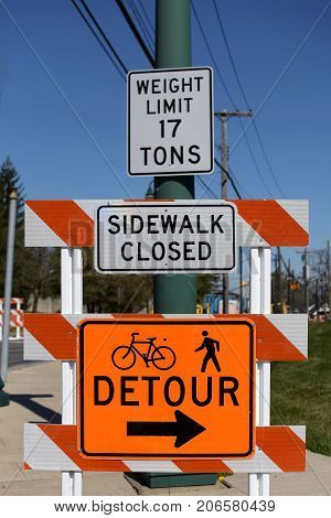sidewalk closed detour construction sign on town street