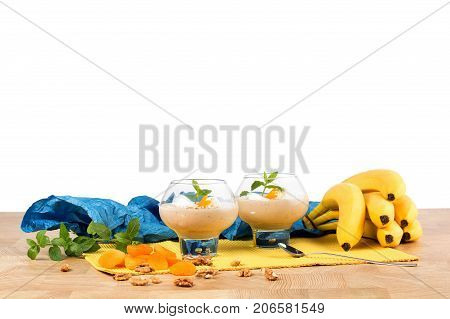Fruity vanilla milkshakes with mint and dried apricots in big glasses isolated on a white background. A colorful composition of heap of bananas, walnuts and peppermint next to milkshakes on a table.
