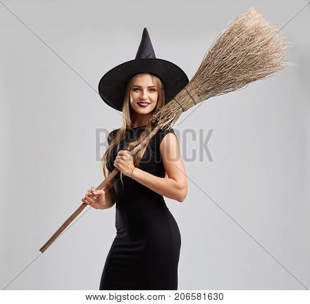 Stunning, gorgeous young witch holding a broomstick ready to fly away. Halloween witch girl in a black haton a light gray background.