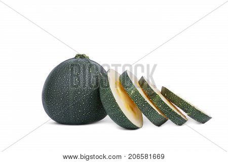 A whole fresh zucchini and slices with yellow seeds, isolated on a white background. Slices of natural and organic dark green zucchini, close-up. Summer ingredients. Copy space.