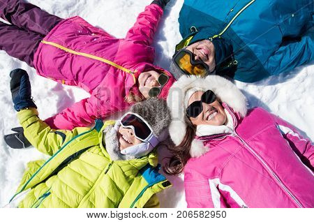 Happy young family lie on snow in winter holiday and looking at camera. High angle view of family in winterwear. Top view of head circle lying on snow and looking up.