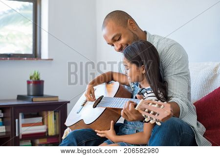 Little girl and black father playing guitar and smiling while sitting on couch at home. African dad teaching daughter to play guitar. Happy father and daughter playing acoustic guitar and enjoying.