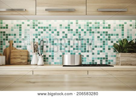 Close up of a light hardwood table surface in a kitchen with green and white mosaic walls wooden consoles and a cooker. 3d rendering copyspace