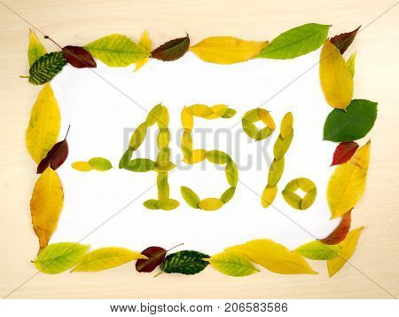 Word 45 percent made of autumn leaves inside of frame of autumn leaves on wood background. Forty five percent sale. Autumn sale template