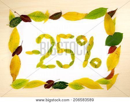 Word 25 percent made of autumn leaves inside of frame of autumn leaves on wood background. Twenty five percent sale. Autumn sale template