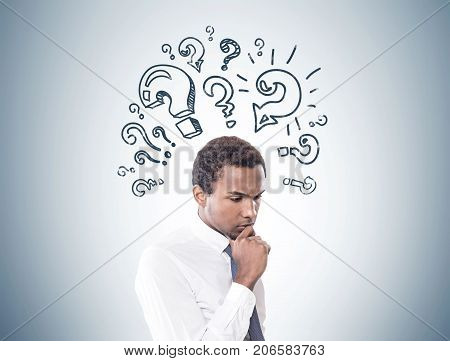 Portrait of a young pensive African American businessman wearing a white shirt and a gray tie. Gray wall background with many question marks on it