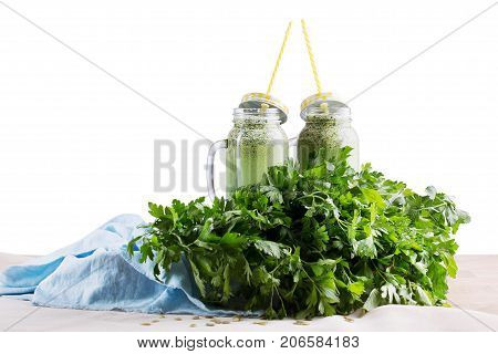 Two big mason jars full of healthful green smoothies on a blue fabric, isolated on a white background. Organic smoothies from celery, parsley, spinach, and cucumber. A lot of green parsley on a desk.