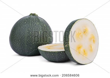 Close-up of two slices of natural and organic zucchini, isolated on a white background. A whole round green zucchini and slices with yellow seeds. Healthful summer ingredients for vegan breakfast.
