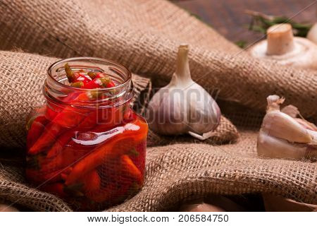 Closeup of red hot chili pepper in a glass shiny jar, white piquant garlic, aromatic mushroom, rural tablecloth, ingredients for spicy dishes on a light wooden background.