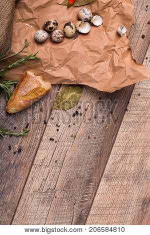 Closeup of fresh white baguette, dried up bay leaves, empty shells of eggs, little quail eggs, different odors seasonings, grocery paper on a wooden light background.
