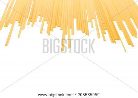 Uncooked long spaghetti isolated on a white background. Macaroni, spaghetti, pasta, noodles for gourmets. A pile of uncooked pasta. Healthful ingredients for nutritious lunches. Copy space.
