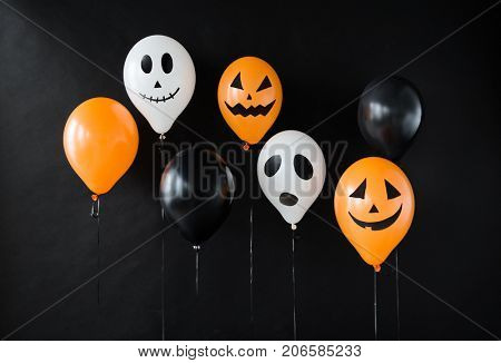 holidays, decoration and party concept - air balloons with funny and evil faces for halloween on black background