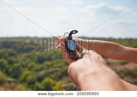 Tourists's hands with compass at mountain road at sunset sky. Close-up view of hand showing little round compass to camera, with incognito man. Point of view shot.