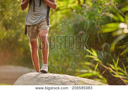 Man travel snikers on nature landscape. Strong legs hiking at mountain peak. Male travel snikers on nature landscape. Healthy hiker walking through the rocky land.