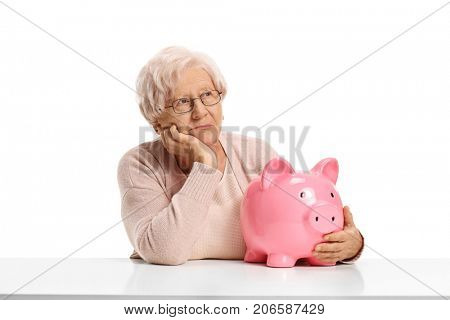 Pensive elderly woman with a piggybank seated at a table isolated on white background