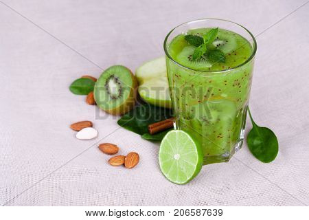 A bright green kiwi smoothie with spicy peppermint and fresh apple on a light table background. Cut in half kiwi with green leaves and nutritious almond nuts. Fruit cocktails for vegetarians.