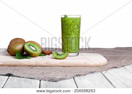 Kiwi fruits full of nutritious vitamins, cinnamon sticks and walnuts on a cloth, isolated on a white background. A smoothie from juicy kiwi, grated nuts, and mint on a cutting board and wooden desk.
