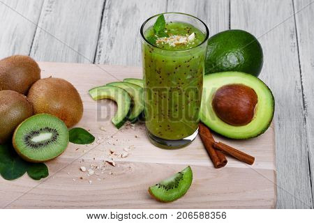 A fantastic composition of vegetarian products on a light cutting desk. Green avocados, sliced kiwis on a gray table background. Nutritious, healthful kiwi juice with aromatic mint and cinnamon.