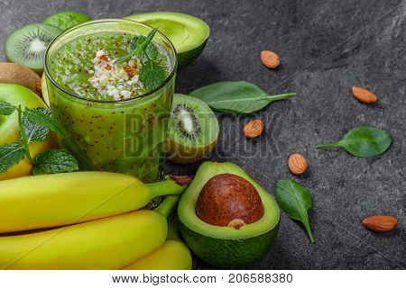 Close-up of different exotic fruits on a gray stone background. A heap of bananas, nutritious avocados, juicy kiwis and peppermint. A tall glass of kiwi beverage with spices and nuts.
