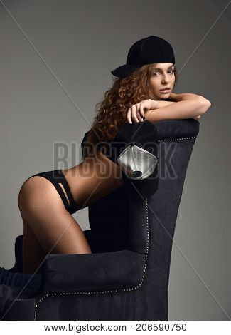 Beautiful luxury fashionable sexy woman sitting on black classic retro chair in long blue boots holding baseball cap on a dark background