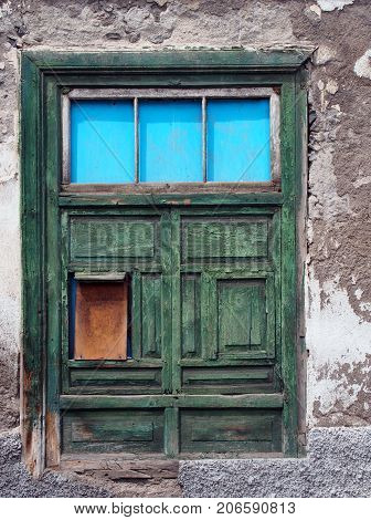 green half shuttered old shabby window in a decaying house with weathered wood and peeling paint set in a white flaking concrete wall