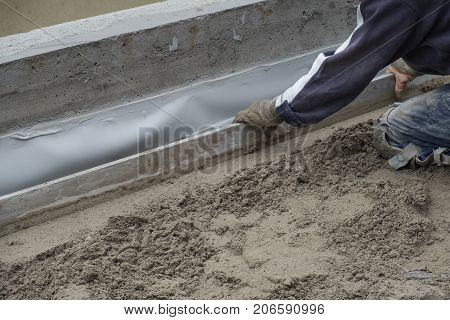 Construction worker kneeling, flattening the cement floor with a hand leveler