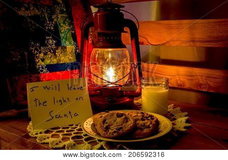 horizontal image of a plate of cookies and milk  put out for Santa with a red lit up lantern shining a light on it with a little child's note for Santa Clause