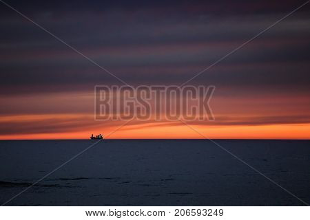 silhouette of a ship high seas at sunset. The sky is beautiful.