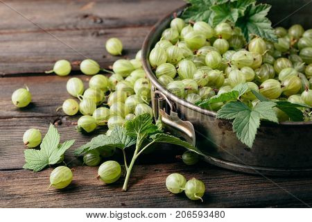 Ripe gooseberry in a plate on a wooden background.