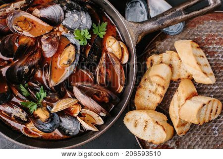 Freshly cooked mussels in sauce in a frying pan with toast. Top view.