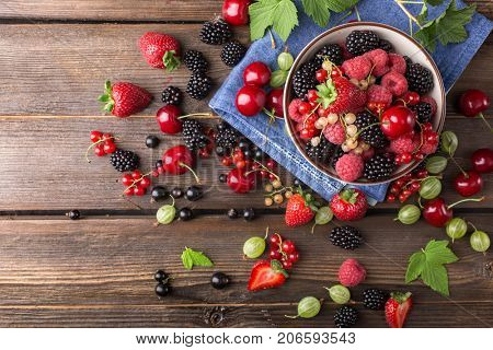 Ripe berries from a garden in a white bowl on a wooden table. Top view