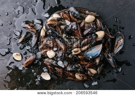 Washed mussels on a metal tray on a dark background. Top view