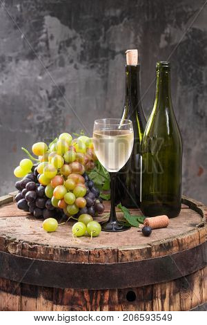 Homemade bottle of wine and a bunch of grapes on a wooden barrel on a dark background