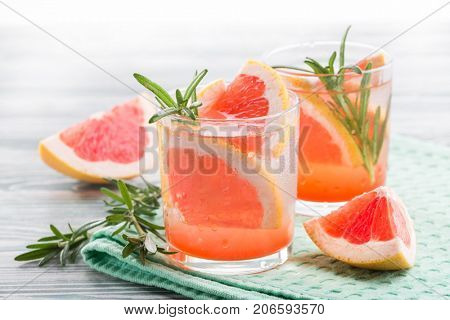 Grapefruit drink with rosemary on a green napkin on a wooden background