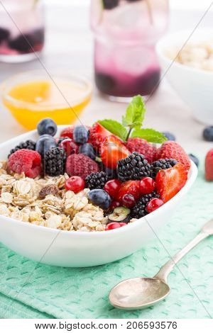 Healthy breakfast. Oatmeal porridge with fresh berries and honey on a green napkin on a wooden table
