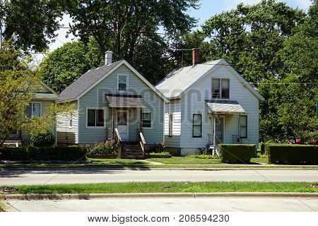 JOLIET, ILLINOIS / UNITED STATES - JULY 25, 2017: Small Cape Cod style houses, built very close together, on Broadway Street, in one of Joliet's less affluent neighborhoods.