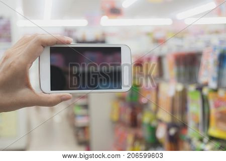 Woman hand holding smart phone in super market shopping blur background.