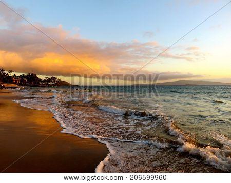 Spectacular Yellow, Orange and Red Tropical Hawaiian Sunset over the Pacific Ocean at Polo Beach Park, Wailea, Maui, Hawaii
